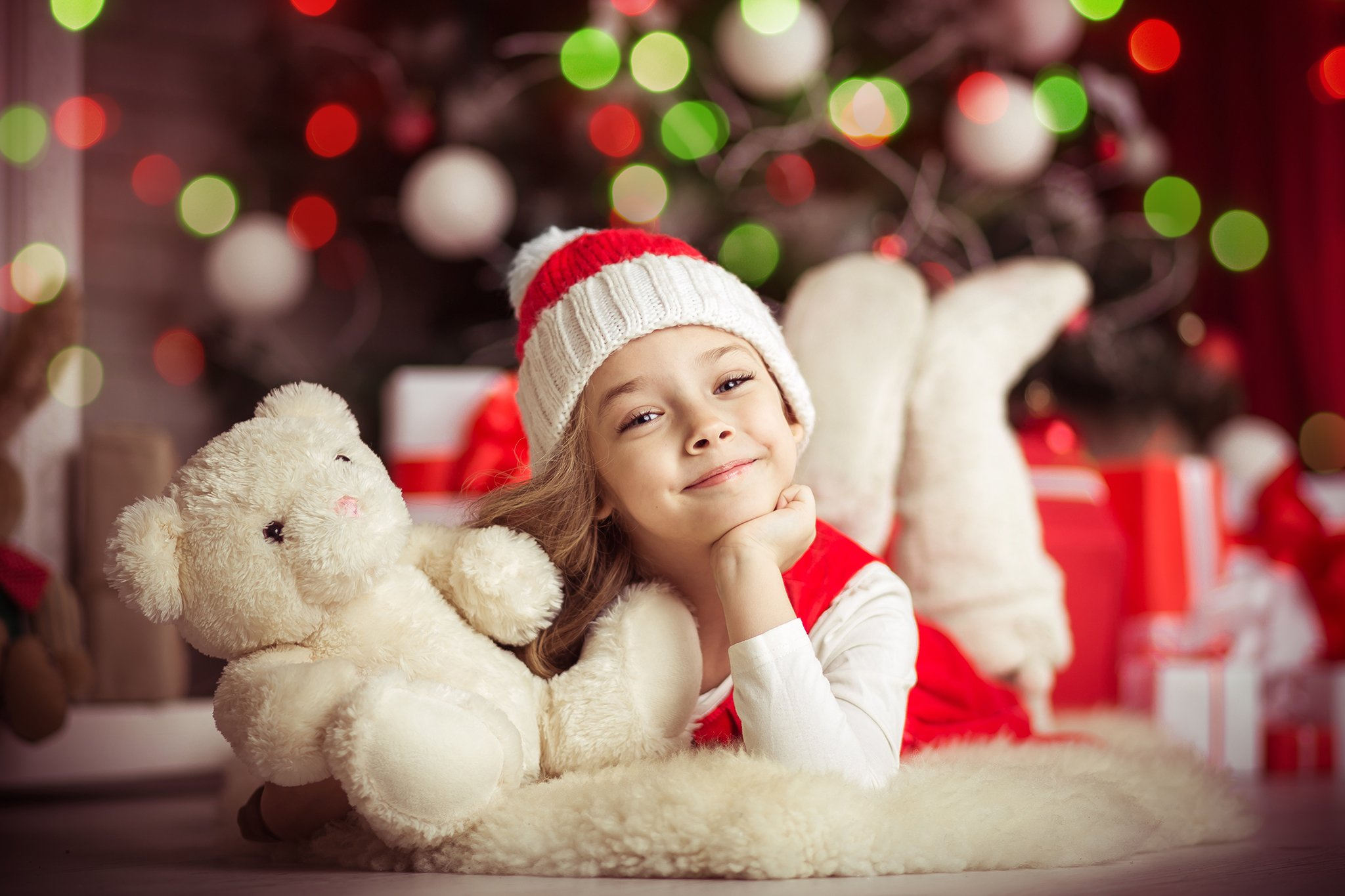 Lovely girl on the floor near the Christmas tree with a bear, studio shot, toning in vintage style.