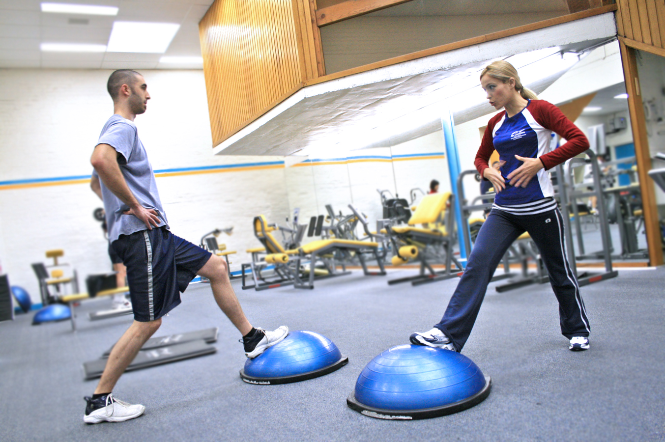 Two_people_in_a_gym_using_BOSU_balls